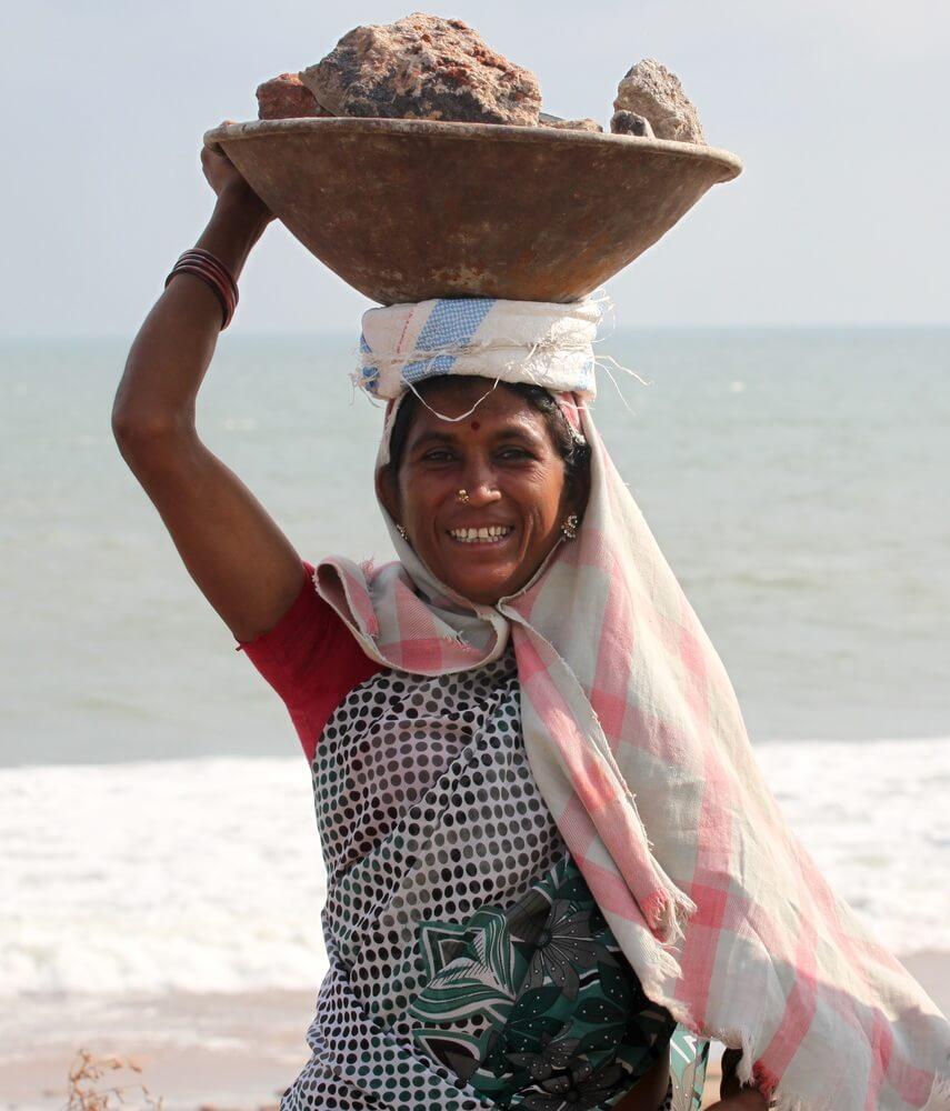 頭で石を運ぶ笑顔の女性