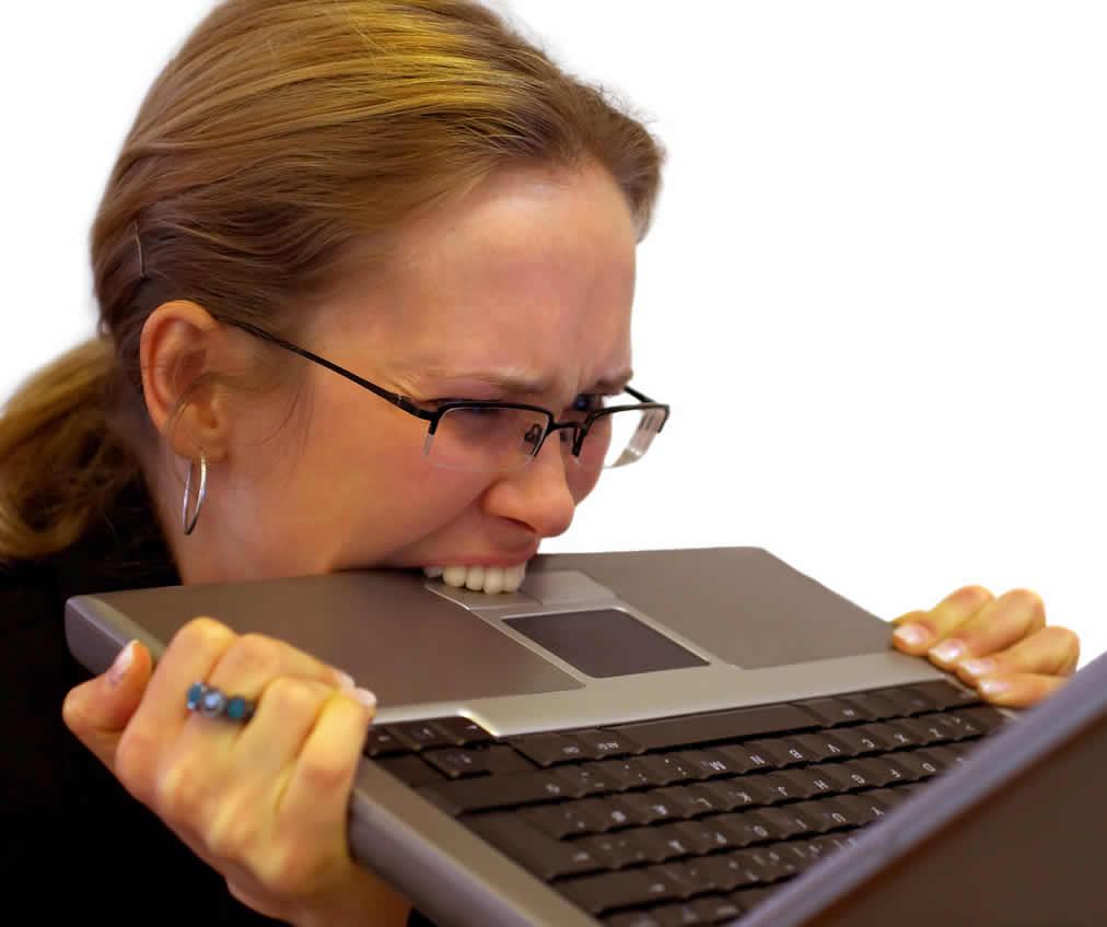 イライラしてパソコンをかじる女性