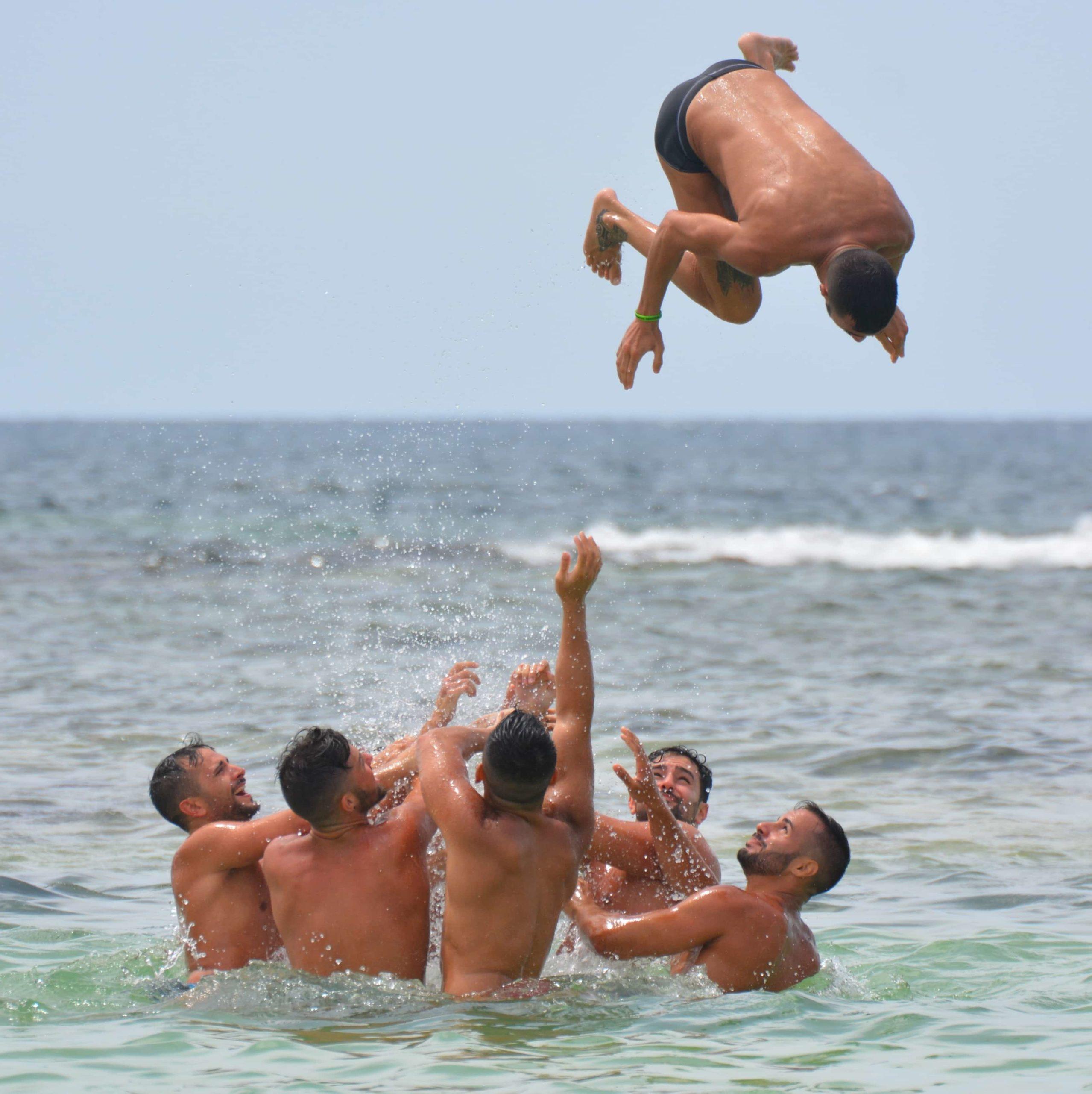 海で友達を投げ上げる男性たち