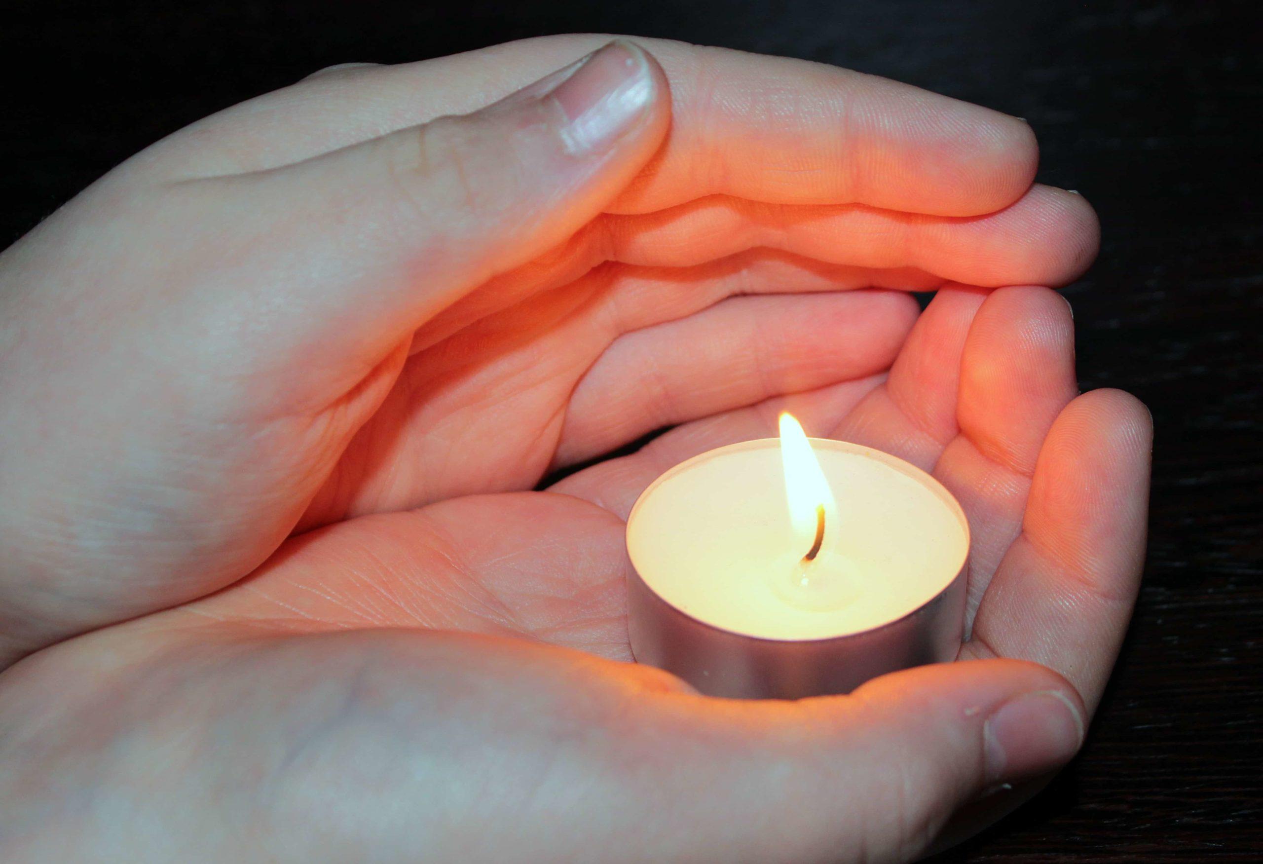 掌のうえのろうそくに灯る弱々しい火