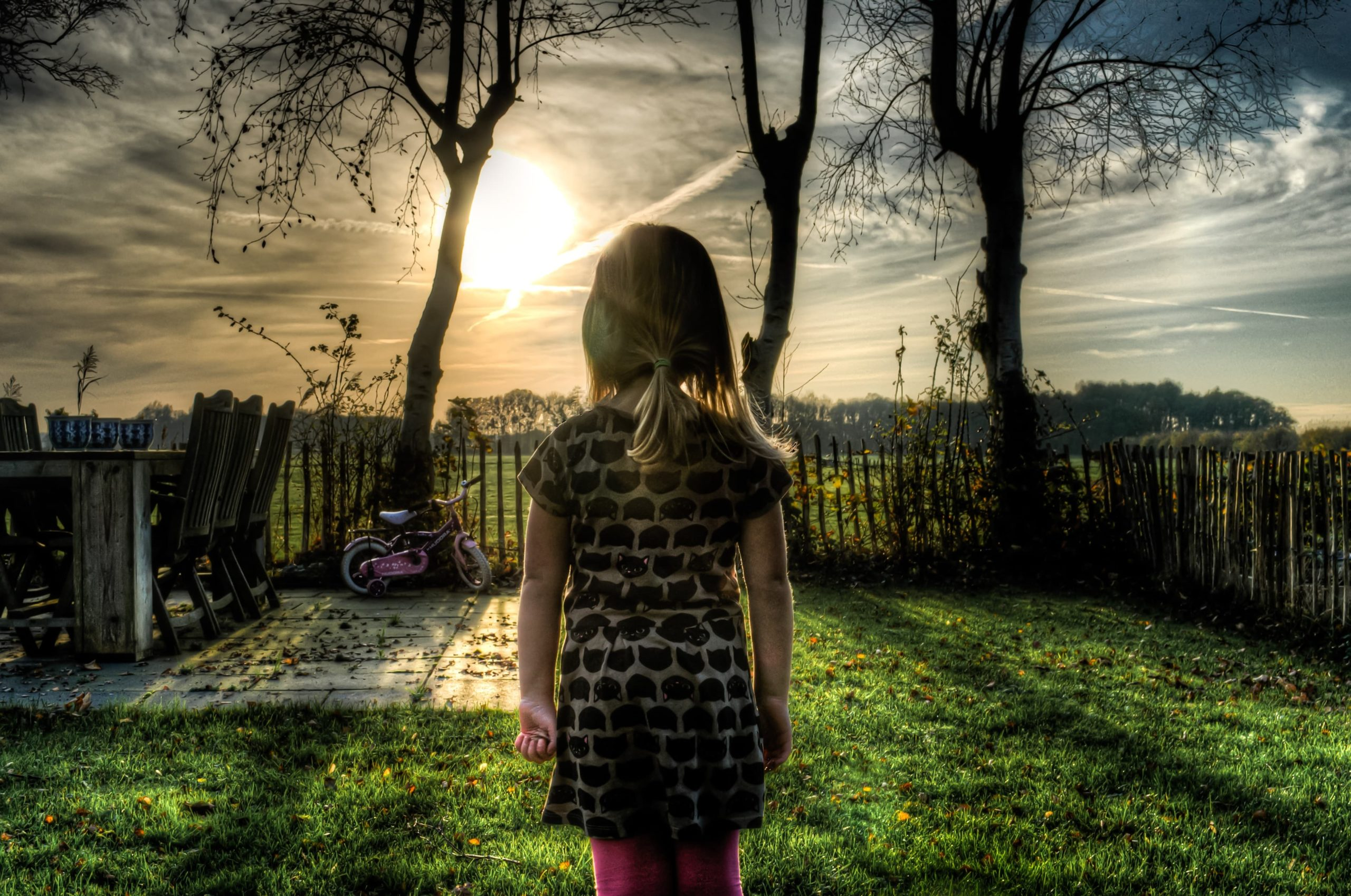 決意とともにじっと立ち、太陽を見つめる女の子