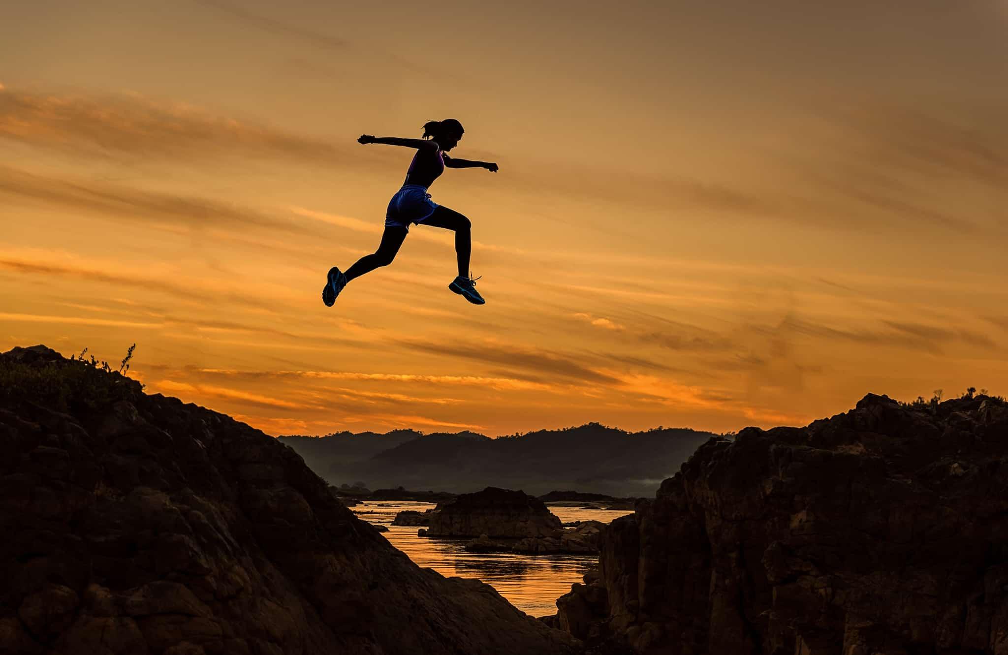 夕暮れの谷を飛び越える女性