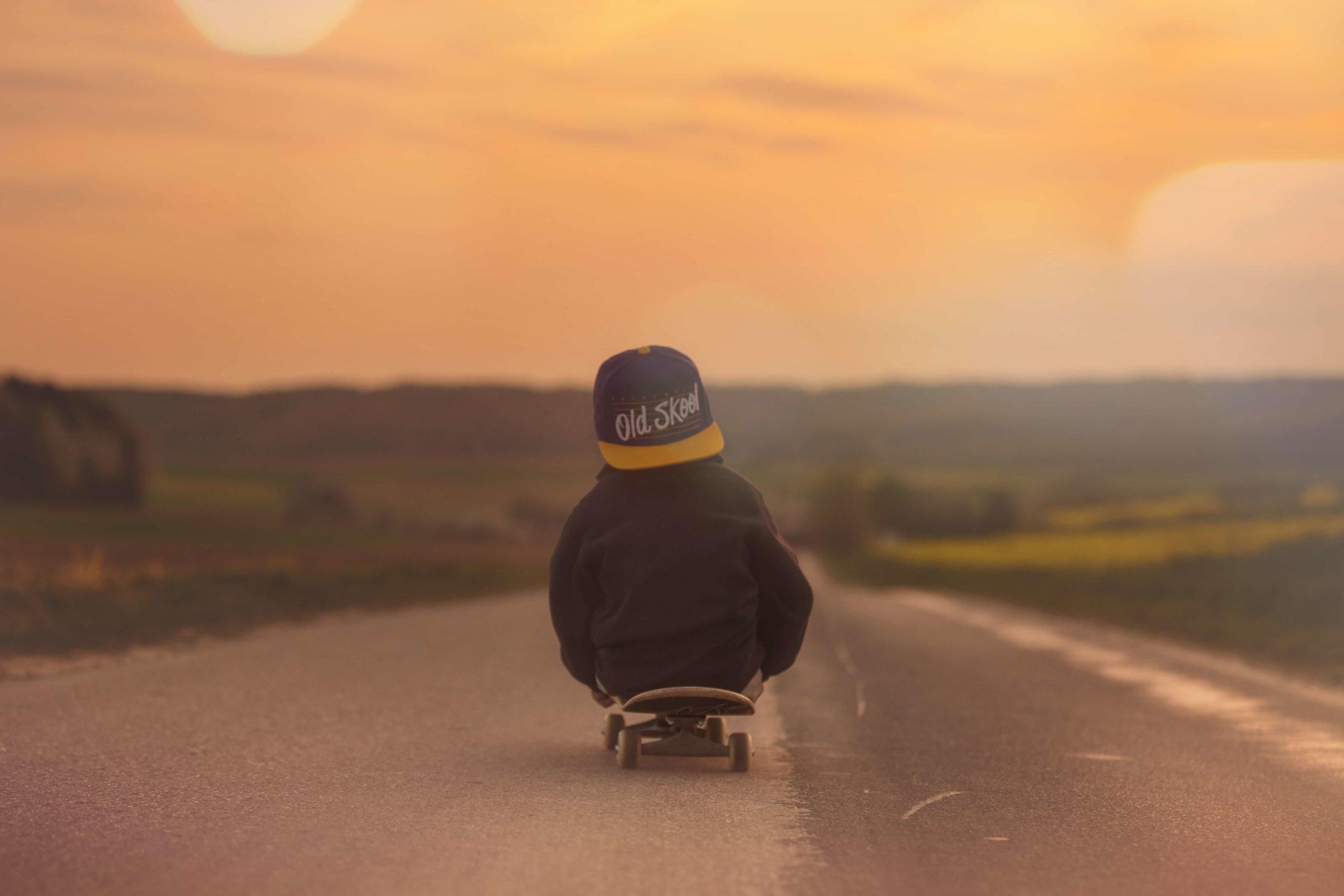 夕暮れの道でスケートボードに座り込む男の子