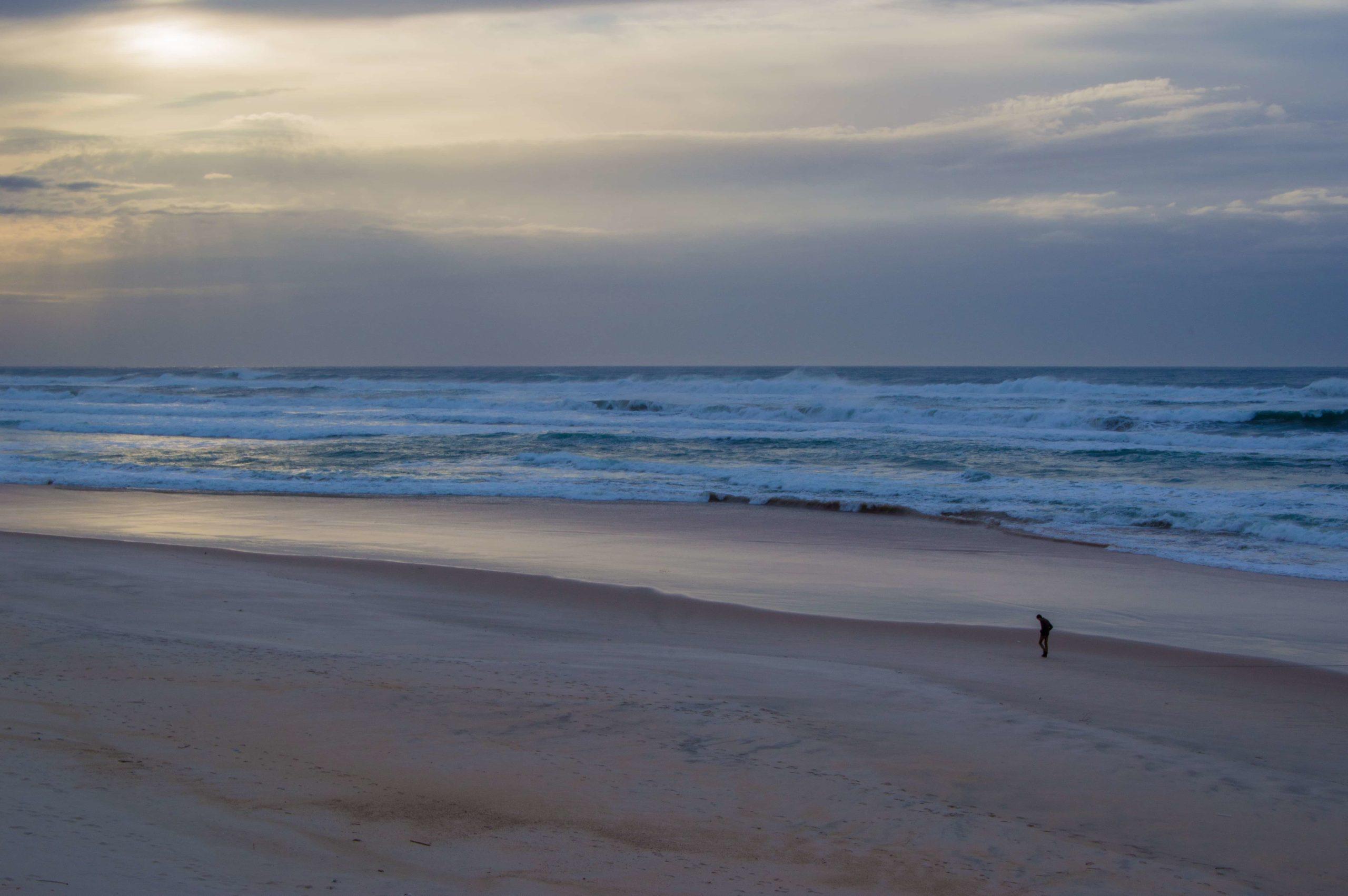 独り浜辺を歩く男性