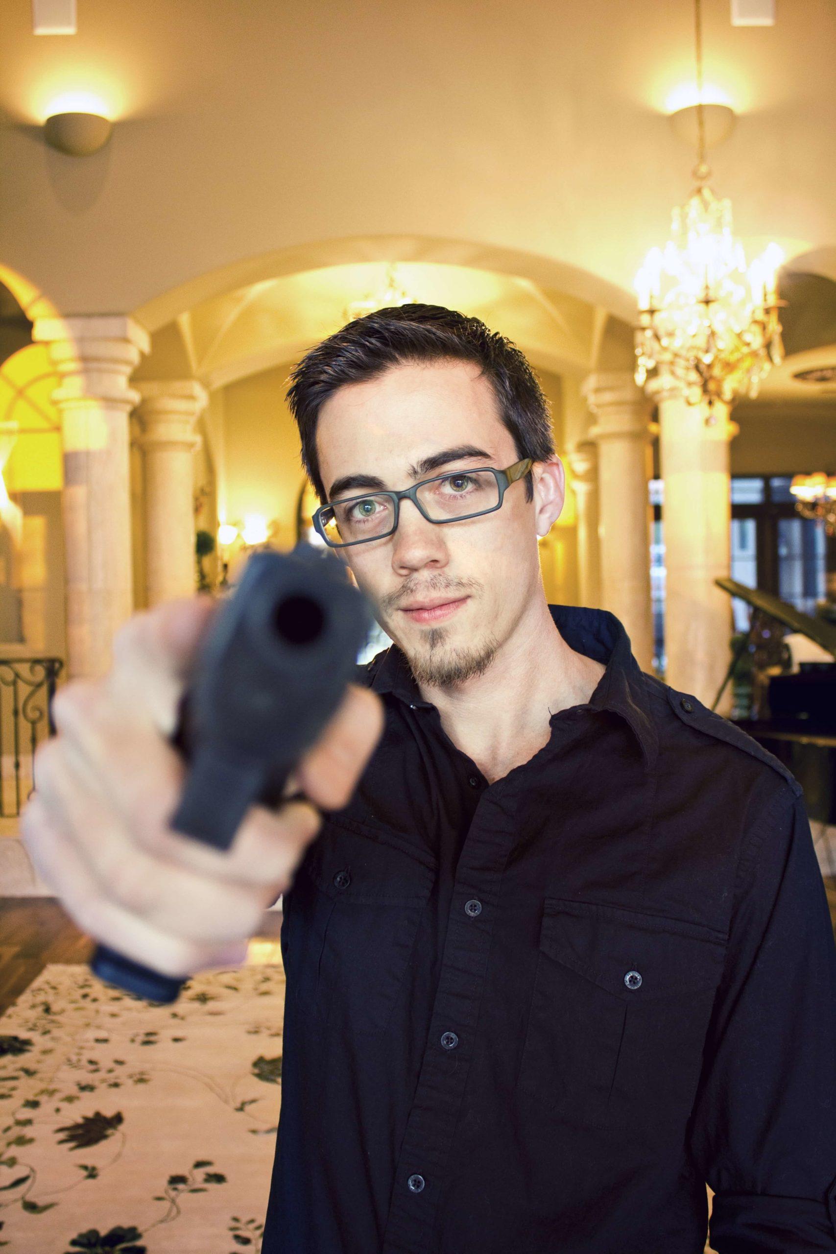 薄笑みを浮かべながら銃口を向けてくる男性