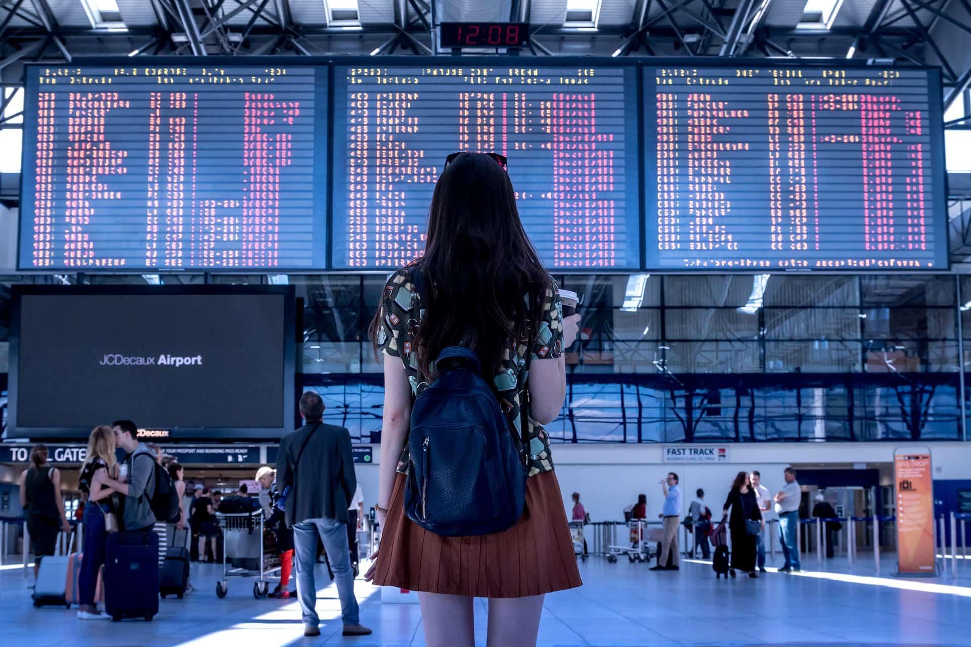空港で搭乗盤を見ている女性