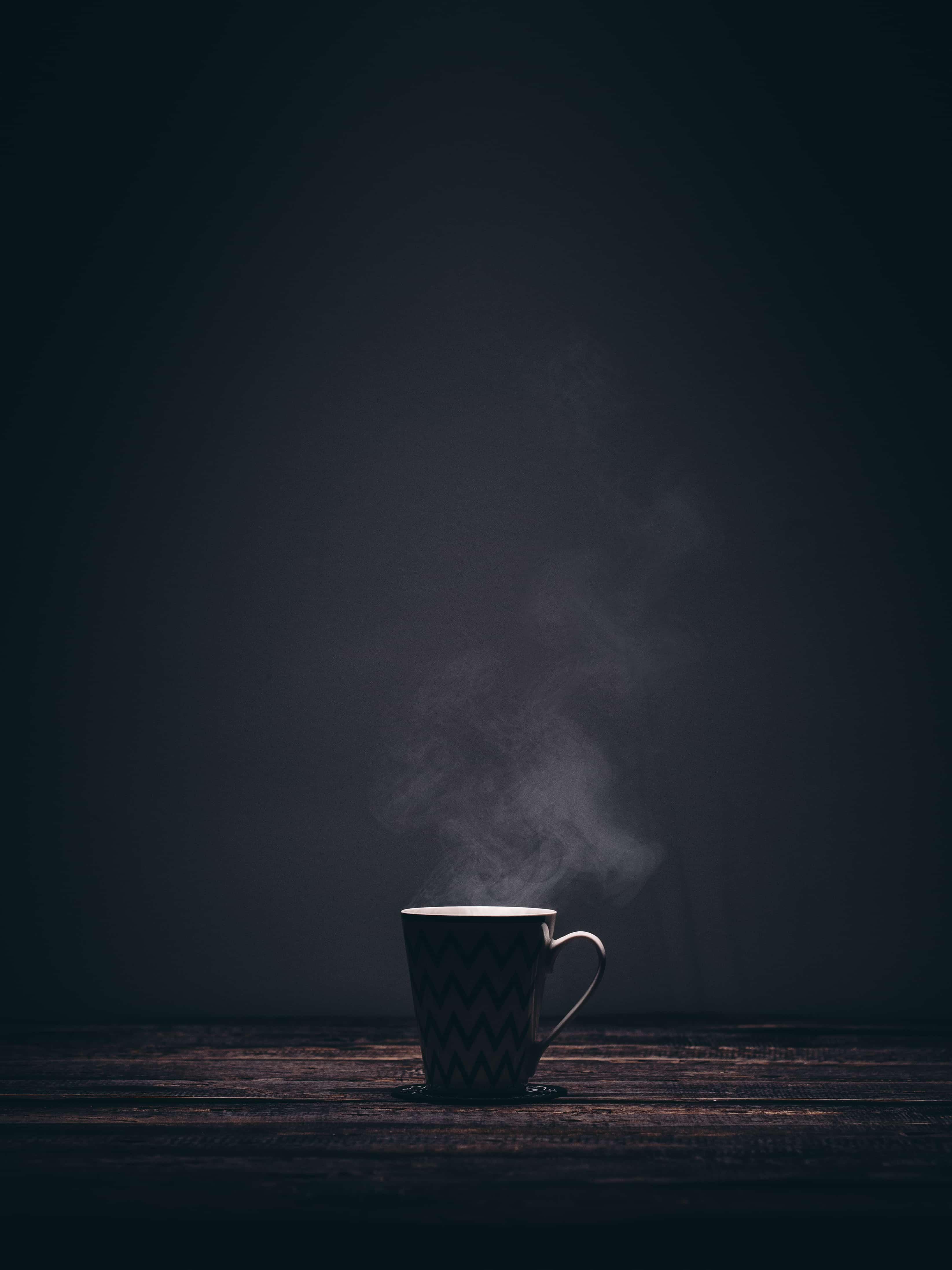 闇に湯気を放つコーヒー