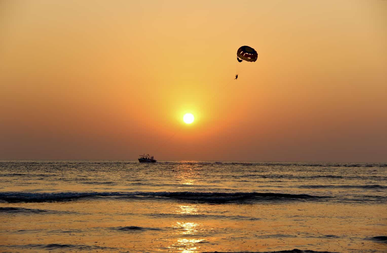 夕暮れの海とパラグライダー