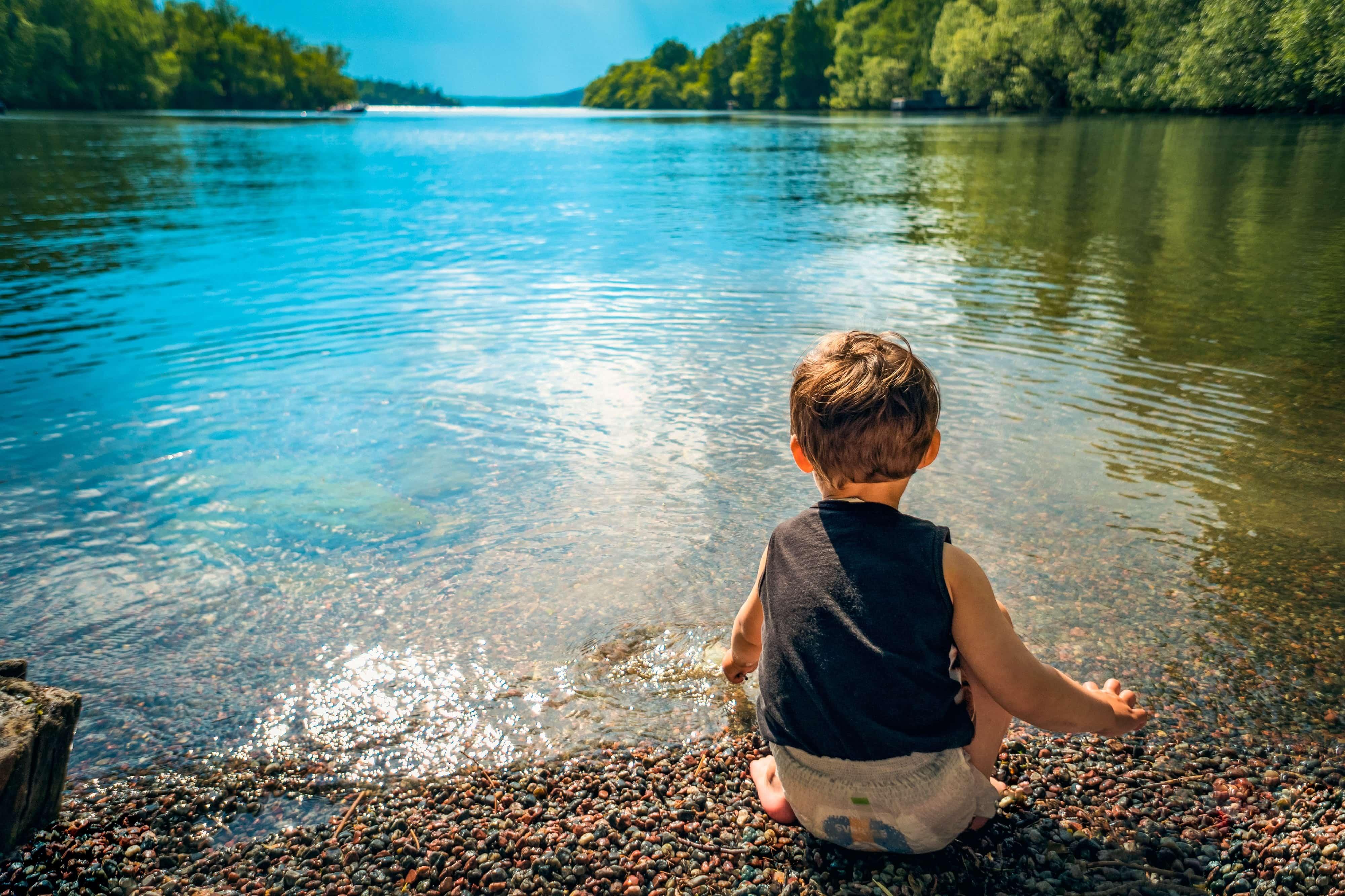 川べりに座る男の子