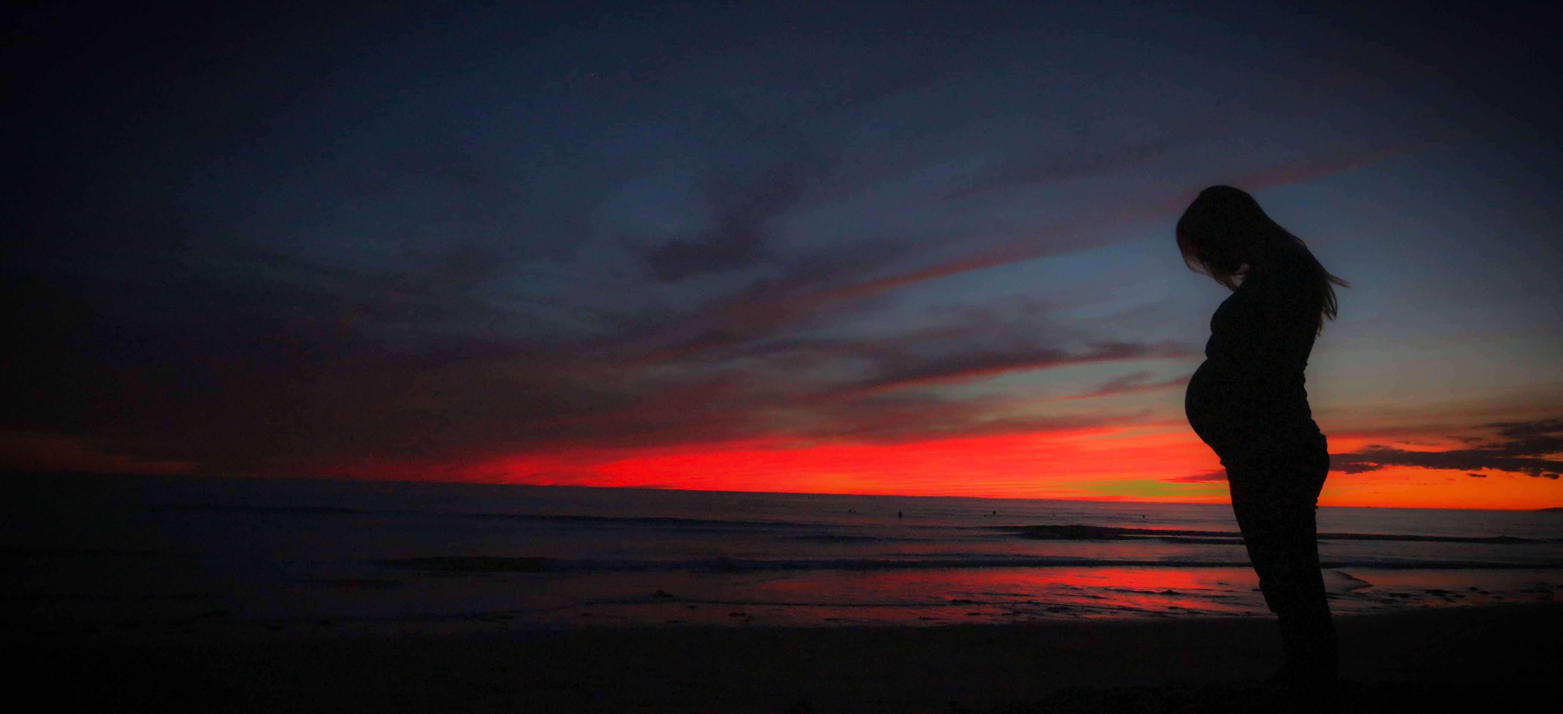 夕暮れの海に立つ妊婦